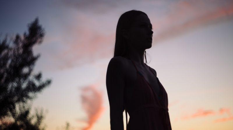 Frau genießt den Sonnenuntergang. Sie steht gerad und hat keine Rückenschmerzen.